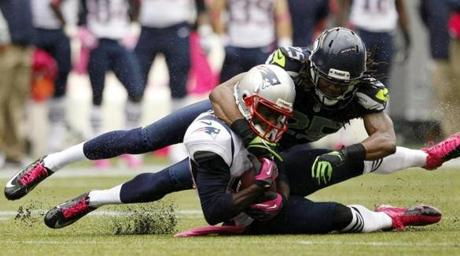Patriots receiver Brandon Lloyd was brought down by Richard Sherman in the first half.